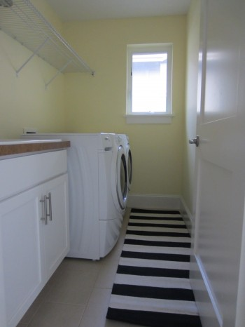 laundry room, yellow laundry room, moonlight benjamin moore, benjamin moore moonlight laundry room, yellow benjamin moore laundry room, black and white rug in laundry room, yellow walls black and white rug